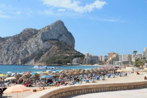 image of a beach with umbrellas set up and people on holiday sunny spain