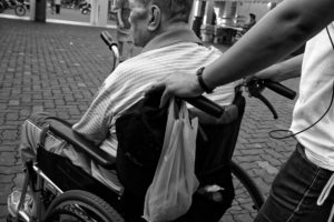 carer pushing patient with disability in a wheelchair